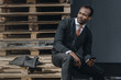 tired stylish african american businessman using smartphone and sitting outdoors