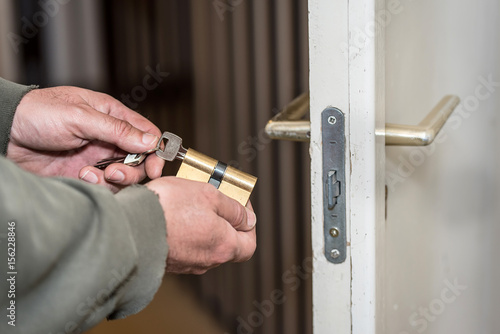 Male handyman worker wood door lock installation or repairing Poster