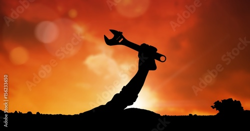 Silhouette hand holding spanner against sky during sunset