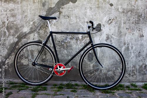 czarny hipster rower w pobliżu szarego betonowego muru