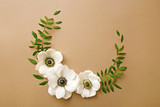 Anemone flowers wreath with green branches. Top view. Neutral background - 156302272