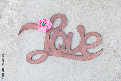 Wooden handwritten sign love on concrete Poster
