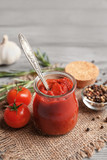 Delicious tomato paste in jar with ingredients on wooden background, closeup