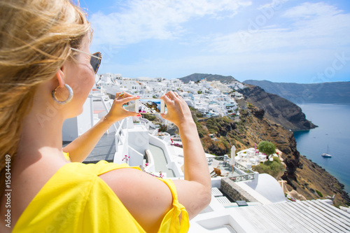 Tourist taking photo of Santorini with mobile phone Poster