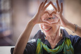 Cute senior old woman making a heart shape with her hands and fingers - 156356632