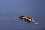 Small towboat pushing two empty barges on broad river - 156431227
