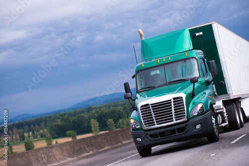 Green Semi Truck With Container Trailer On Highway