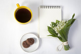 yellow cup of coffee, a bouquet of lilies of the valley, a notepad for notes and a saucer with two brownie cookies. Breakfast. Copy space