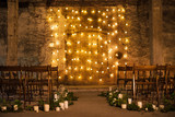 Wedding ceremony decorations in loft grunge surround. Light bulb garland, candles, glass and chairs - 156492819