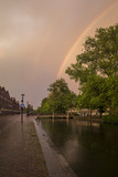 Dramatic sky with a rainbow over a canal in Amsterdam, The Netherlands