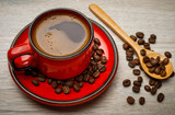 A red cup of tasty coffee with coffee beans, on wooden background