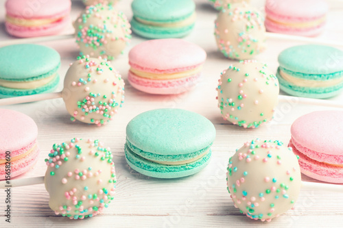 Poster Sweet background of mint and strawberry flavor macaroons and cake pops on sticks