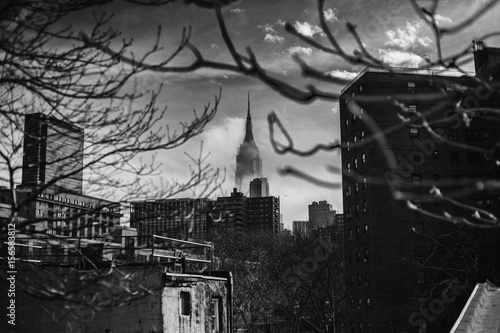 Creepy black and white shot of Empire State Building in hazy sky Poster