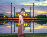 female woman muslim pray in front of mosque in Ramadan Kareem at sunset scenery