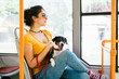 Quadro Beautiful young woman sitting in city bus with her jack russell terrier.