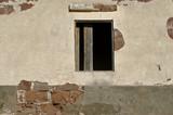 Eine alte Hauswand mit einer Fensteröffnung und Brettern.