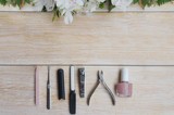 Manicure and pedicure accessories on wooden background with flower frame. Diamond nail file, stone file cuticle remover, nail clipper and nude nail polish.Copy space.