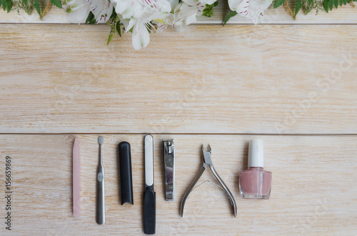 Fotobehang Pedicure Manicure and pedicure accessories on wooden background with flower frame. Diamond nail file, stone file cuticle remover, nail clipper and nude nail polish.Copy space.
