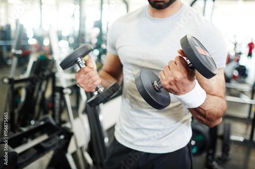 Muscular athlete sweating while pumping biceps