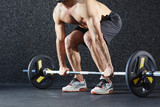 Active athlete lifting weight from floor
