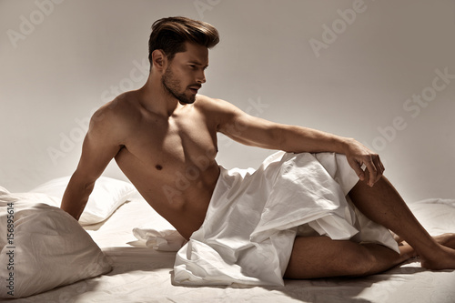 Tuinposter Artist KB Handsome, muscular man posing on the soft bed
