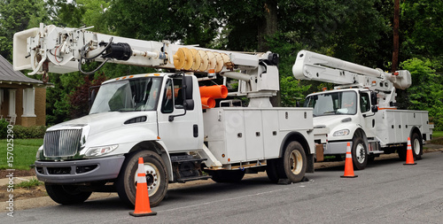 Front and side view of parked communication utility trucks in residential neighborhood. Horizontal. - 157025290