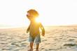 Little black girl on sandy beach in sunset lights