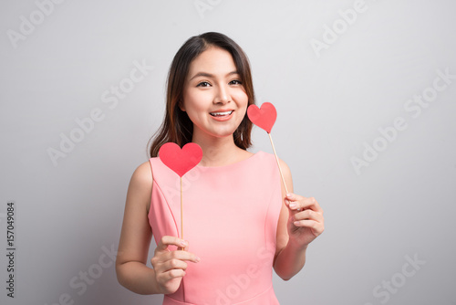 Charming asian woman holding red heart shape.