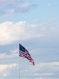 Vertical photo of American Flag against gray and white cumulus clouds and blue sky. The flag is unfurled in the breeze. - 157098655