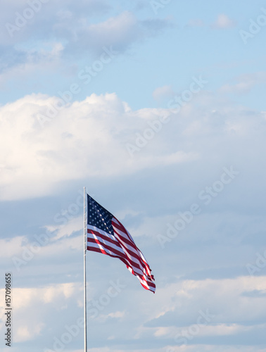 Poster Vertical photo of American Flag against gray and white cumulus clouds and blue sky