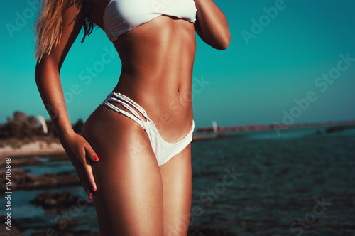 Athletic shaped woman showing summer hot body on the beach