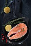 Top view of raw fresh salmon fillet in a frying pan, vertical shot over black wooden background