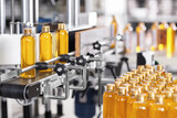 Production line of beauty and healthcare products at plant or factory. Process of manufacturing and packaging cosmetics goods. Glass or plastic bottles with screw caps standing on conveyor belt - 157125815