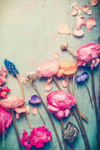 Pretty flowers retro pastel toned on vintage turquoise background, top view