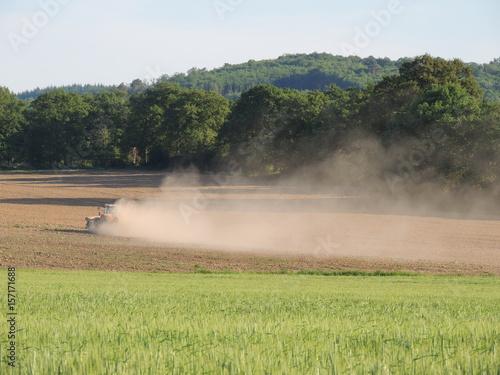 Tracteur travaillant un champ très sec et soulevant un nuage de poussière