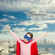 Quadro Cute little super hero girl in the red cloak against the urban background