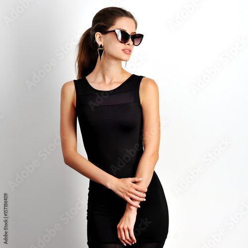 female in black dress and sunglasses posing