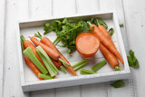 Carrot and celery juice with fresh vegetables and herbs in white wooden tray