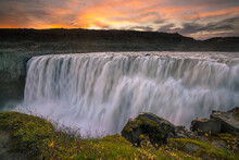 Detifoss waterfall with sunset in the background