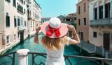 Venezia, donna con cappello sul ponte e canale, italia