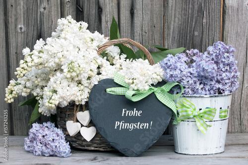 """Text """"Frohe Pfingsten"""" auf Schieferherz mit Flieder rustikal vor Holzhintergrund"""