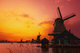 Traditional Dutch windmills on the canal bank at warm sunset light in Netherlands near Amsterdam