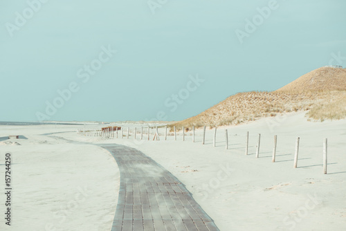 Boardwalk on a empty beach with dunes and grass in notrh Nethelands at windy day - 157244250