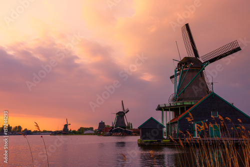 Traditional Dutch windmills on the canal bank at warm sunset in Netherlands near Poster