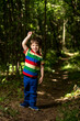 young boy playing in the green forest
