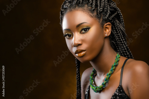 Studio portrait of attractive african woman with braids.