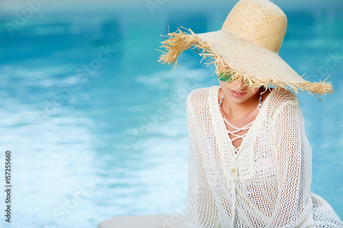 Beautiful girl in a  dress and sunhat sits next a resort pool