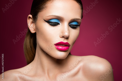 Poster Beautiful young female face with bright fashion multicolored make-up on a pink b