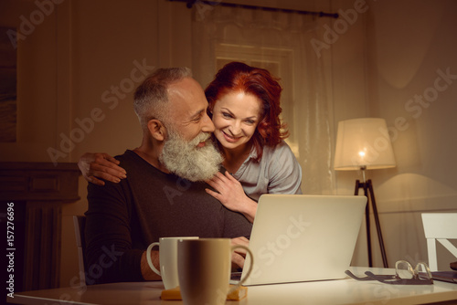 smiling middle aged couple looking at laptop at home