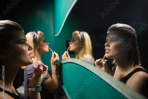 Two women applying lip gloss while looking at mirror Poster